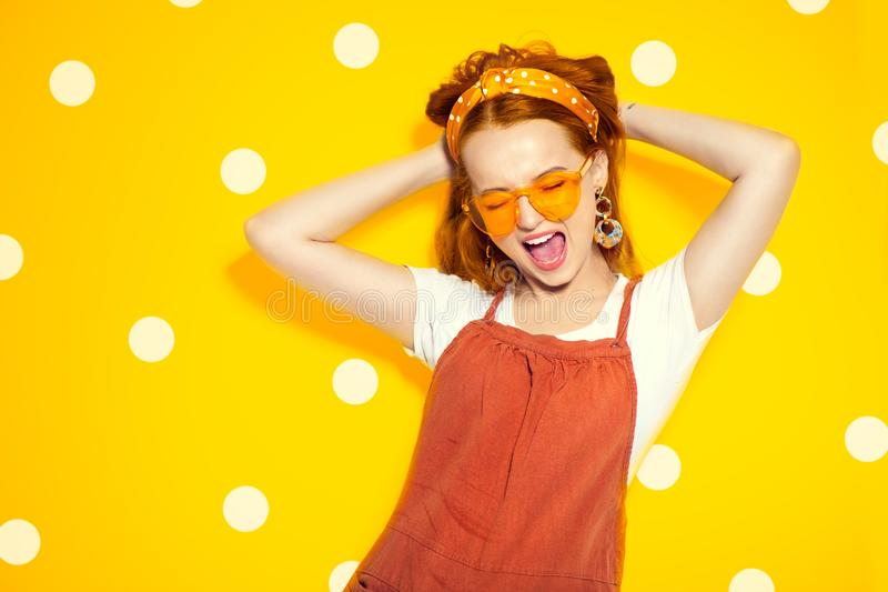 Fashion model girl over yellow polka dots background. Beauty stylish redhead woman posing in urban clothes and yellow sunglasses stock photos