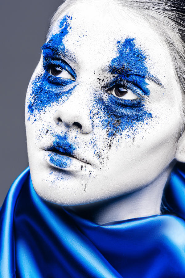 Fashion model girl portrait with colorful powder make up. woman with bright blue makeup and white skin. Abstract fantasy stock image