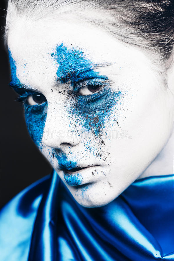 Fashion model girl portrait with colorful powder make up. woman with bright blue makeup and white skin. Abstract fantasy royalty free stock image