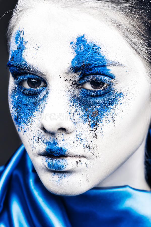 Fashion model girl portrait with colorful powder make up. woman with bright blue makeup and white skin. Abstract fantasy stock photography