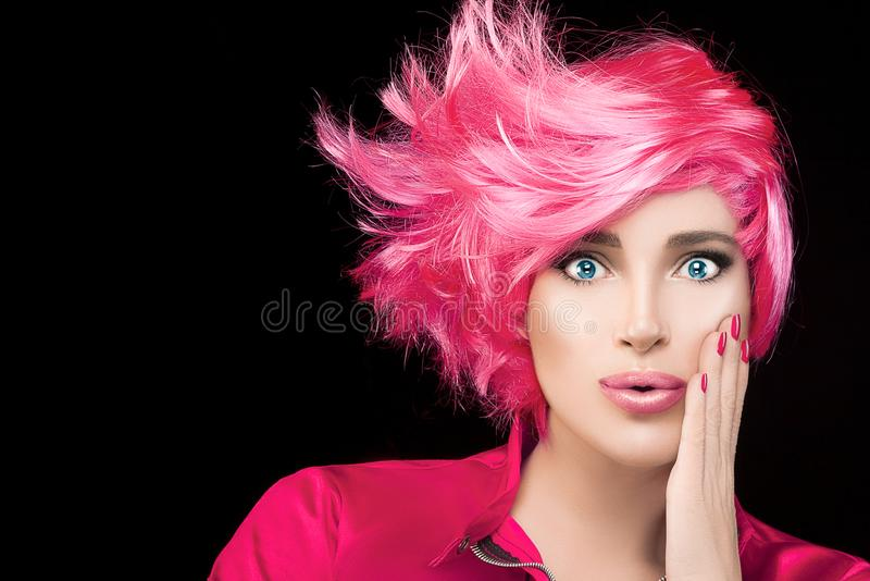 Fashion model girl with stylish dyed pink hair. And pursed lips with expression of surprise looking at camera. Beauty Hairstyle portrait isolated on black royalty free stock image