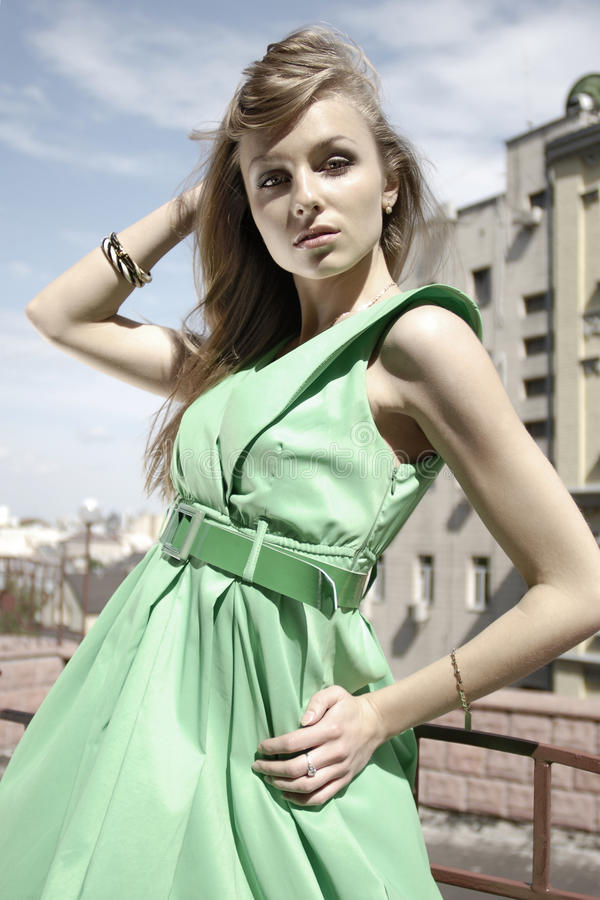Fashion model in green. Cross-processed portrait of a pretty fashion model in green dress on the street royalty free stock photos