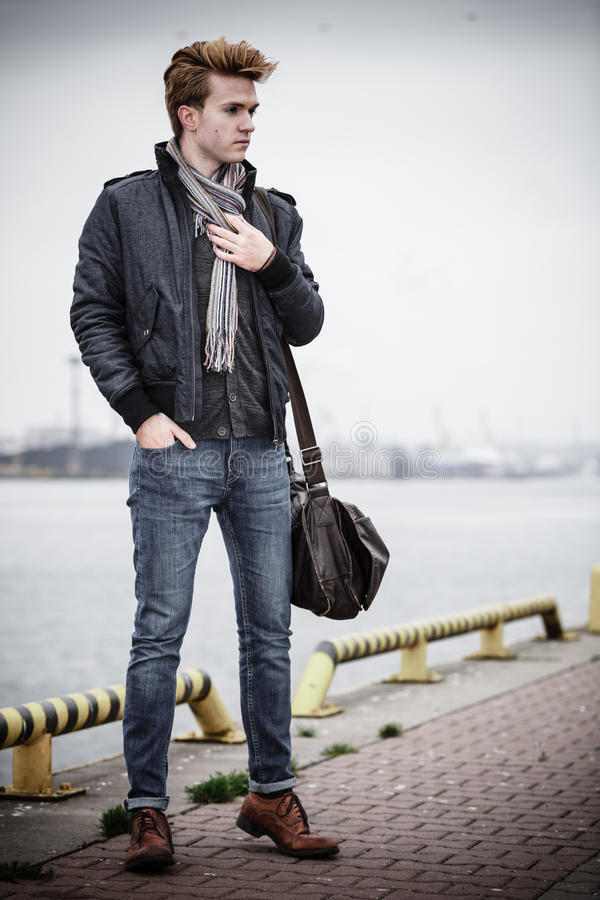 Fashion model guy with bag outdoors. Full length young handsome man fashion model casual style with bag on street urban industrial background royalty free stock images