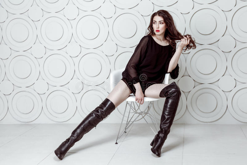 Fashion model with hairstyle and smokey makeup and red lips in black dress and boots posing on white chair. Studio shot stock photos