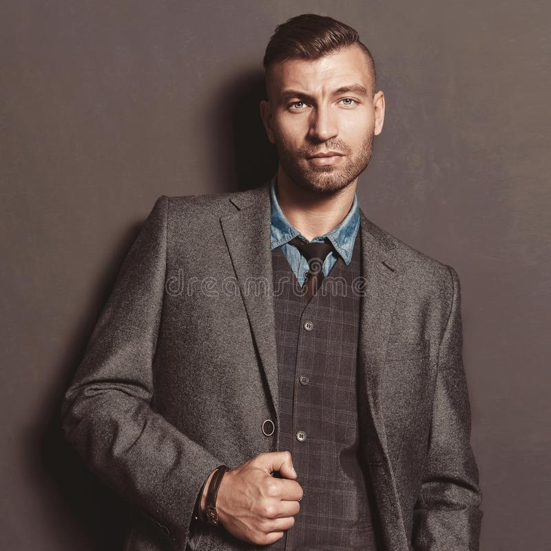 Fashion model handsome stylish man in suit on gray wall background. Elegant fashionable beautiful brutal man stock image