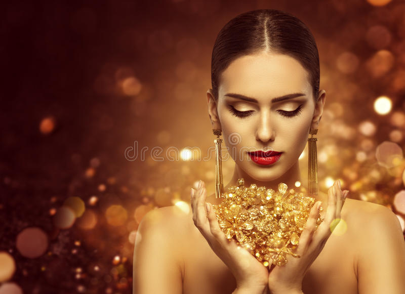 Fashion Model Holding Gold Jewelry in Hands, Woman Golden Beauty stock photography