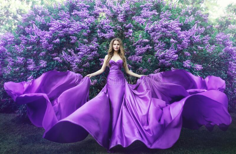 Fashion Model in Lilac Flowers, Young Woman in Beautiful Long Dress Waving on Wind, Outdoor Beauty Portrait in Blooming Garden royalty free stock photos