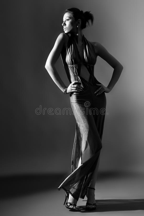 Fashion model in long clothes on dark background royalty free stock image