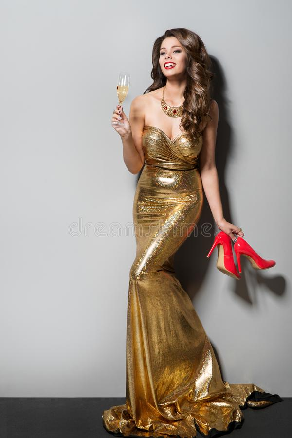 Fashion Model in Long Gold Dress Dancing and Drinking, Happy Elegant Woman, High Heel Shoes royalty free stock photography