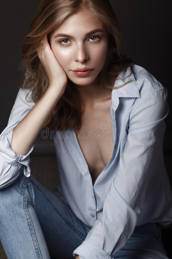 Fashion model with long hair, perfect skin is posing in studio for glamour test photo shoot showing different poses. Fashion model with long hair, beautiful eyes royalty free stock photo