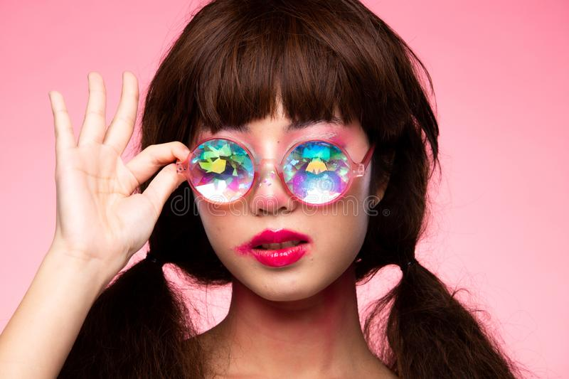 Fashion Model Woman wear Kaleidoscope Glasses. Fashion Model looks at camera for shooting new collection Sunglasses.  Beautiful Asian Woman summer trend make up stock image