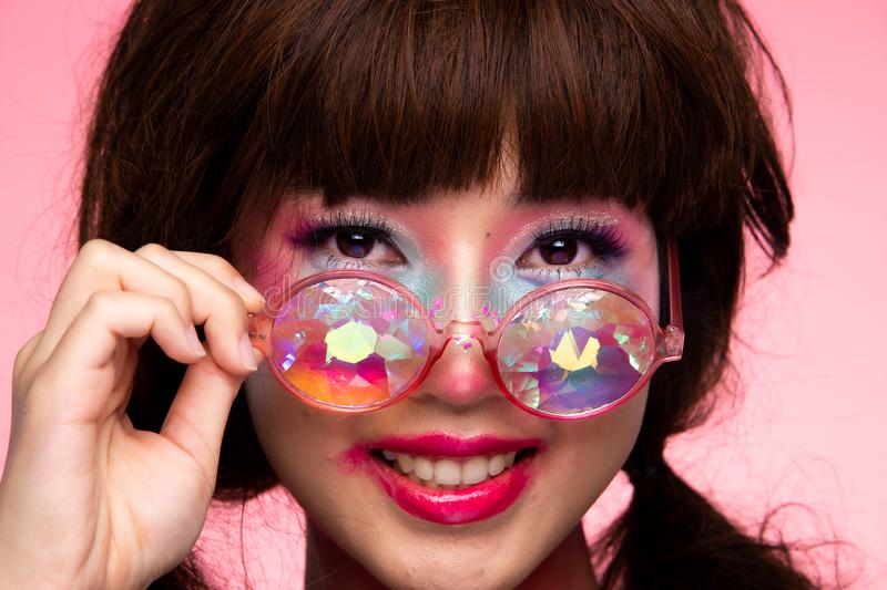 Fashion Model Woman wear Kaleidoscope Glasses. Fashion Model looks at camera for shooting new collection Sunglasses.  Beautiful Asian Woman summer trend make up royalty free stock images