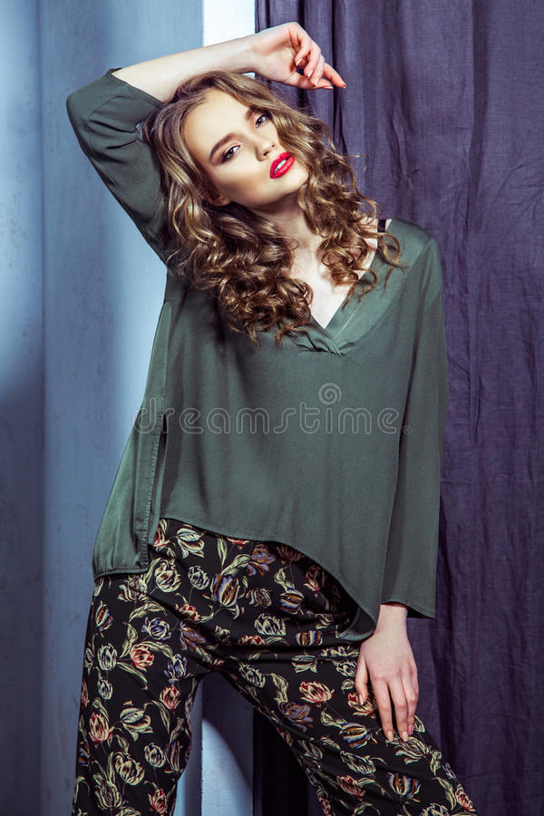 Fashion model with makeup and wavy hairstyle is posing in fitting room.  stock photos