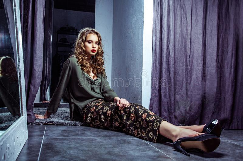 Fashion model with makeup and wavy hairstyle in stylish clothes and high heels shoes sitting on dark gray floor in fitting room. And looking at camera with royalty free stock image