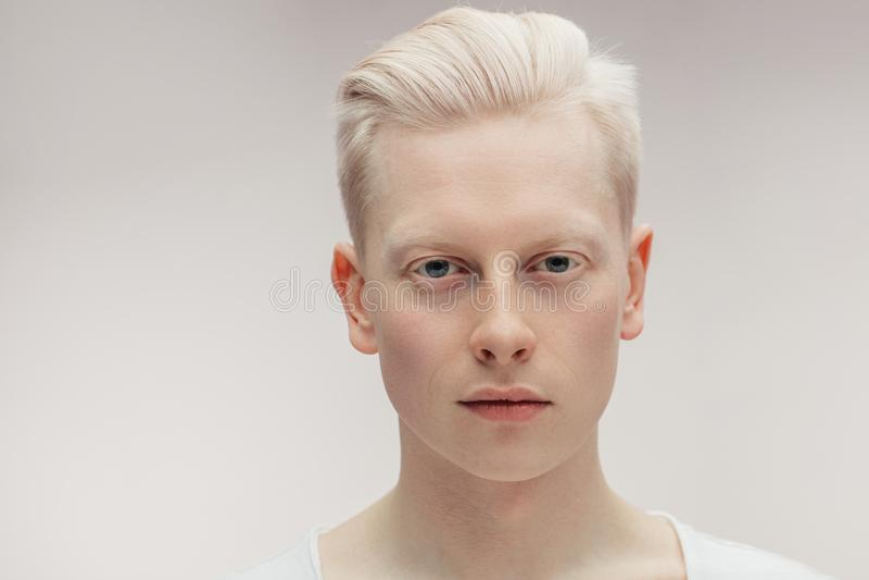 Fashion model male on white. Handsome albino guy closeup. stock photo