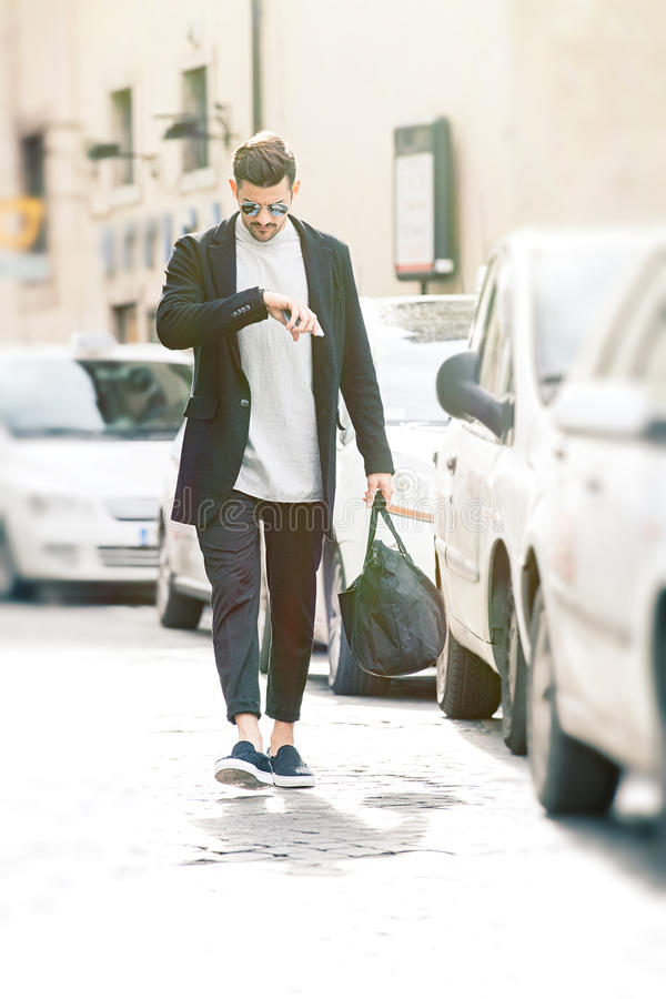 Fashion model man checking watch. Appointment in the city stock images