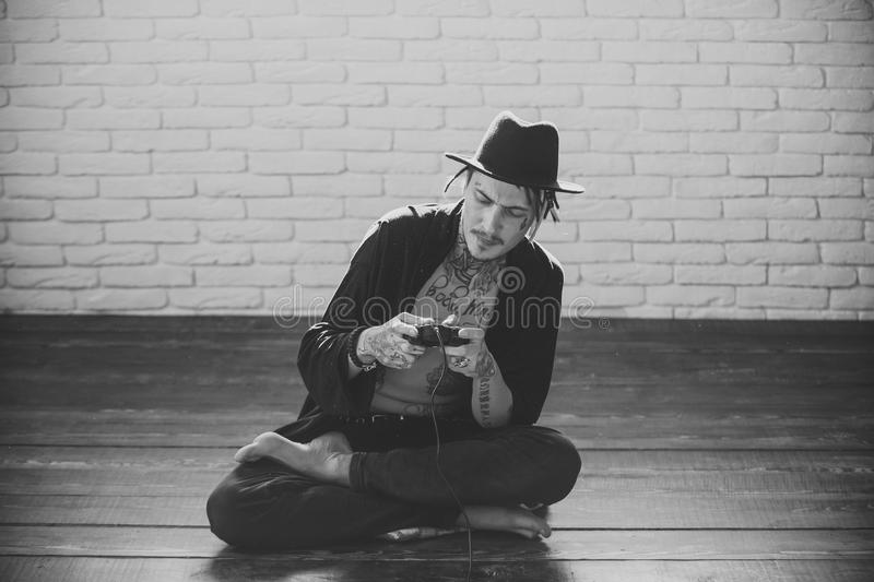 Fashion model Man fece close up. Face Man wiht happy Man holding video console in hands. Gamer in hat with tattooed torso sitting on wooden floor royalty free stock photography
