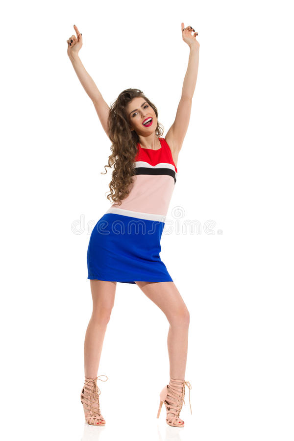 Fashion Model In Mini Dress And High Heels Is Posing With Arms Raised. Beautiful young woman in colorful mini dress and high heels is standing legs apart and royalty free stock photos