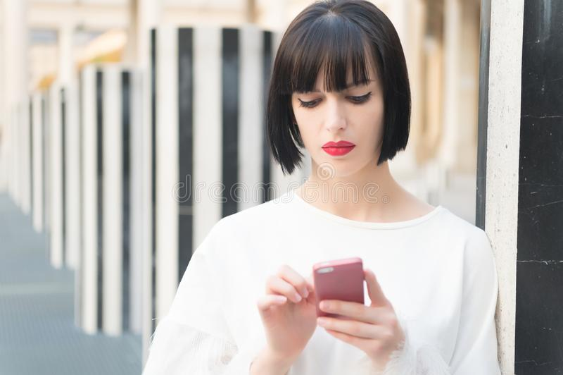 Fashion model with mobile device. Woman with red lips use on smartphone in paris, france. Woman with brunette hair hold mobile pho royalty free stock photography