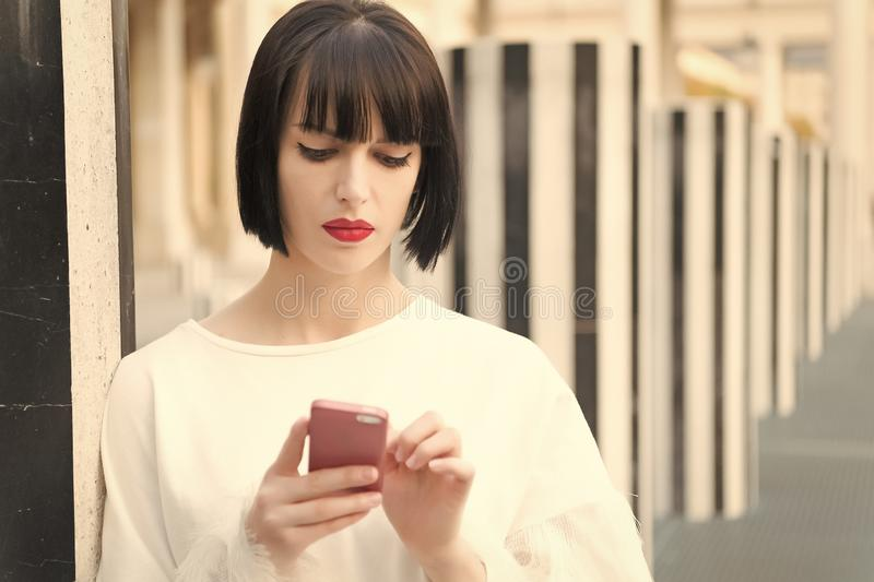 Fashion model with mobile device. Woman with red lips use on smartphone in paris, france. Woman with brunette hair hold royalty free stock images