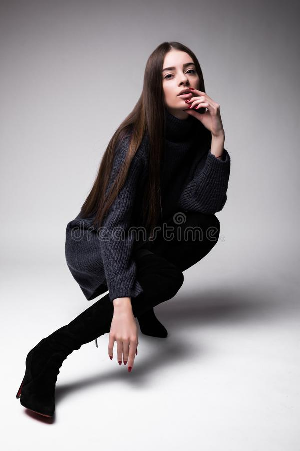 Fashion model woman in modern clothes sitting on the floor isolated on white background stock photos