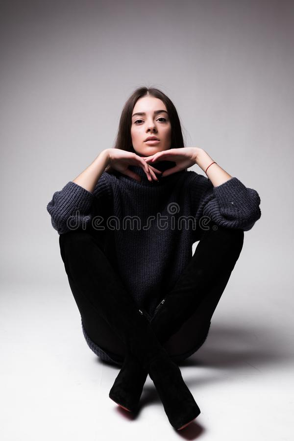 Fashion model woman in modern clothes sitting on the floor isolated on white background royalty free stock photos