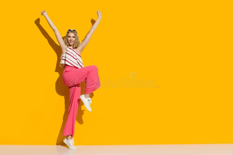Happy Young Woman In Pink Wide Leg Trousers And Striped Top Is Standing On One Leg With Arms Raised stock photography
