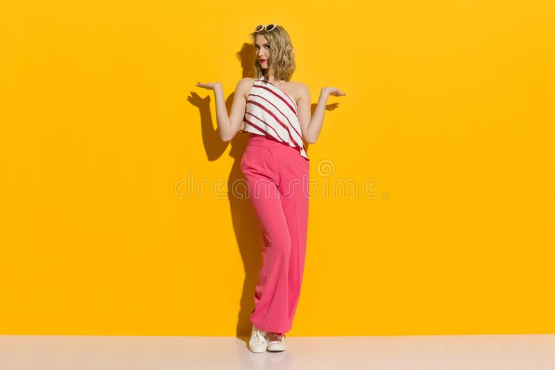 Stylish Young Woman In Pink Wide Leg Trousers Is Standing In The Sunlight And Presenting stock photos