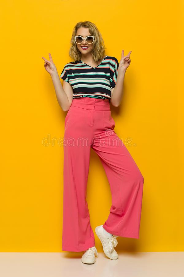 Fashion Model In Pink Wide Legs Trousers And Sunglasses Is Showing Peace Hand Sign. Young woman in sunglasses and striped blouse and pink wide legs trousers is stock photography