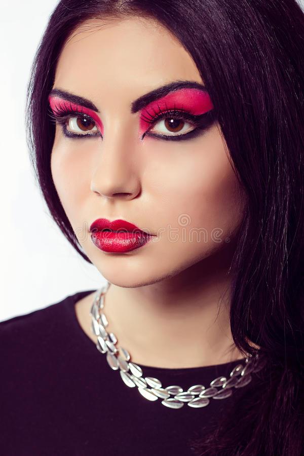 Fashion model portrait. Scarlet makeup. Black arrows. Close up portrait of young beautiful brown-eyed woman with long black hair on white background. Arab woman royalty free stock photo