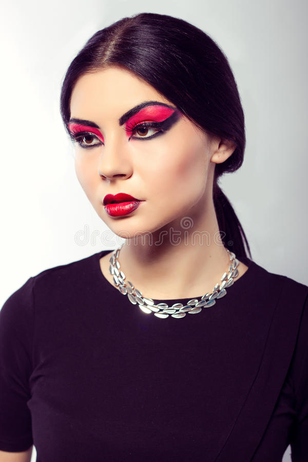 Fashion model portrait. Scarlet makeup. Black arrows. Close up portrait of young beautiful brown-eyed woman with long black hair on white background. Arab woman royalty free stock image