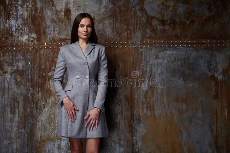Fashion model pose for catalog fall collection designer clothes. Casual long grey dress office party walk meeting pretty beauty woman brunette hair natural royalty free stock photo