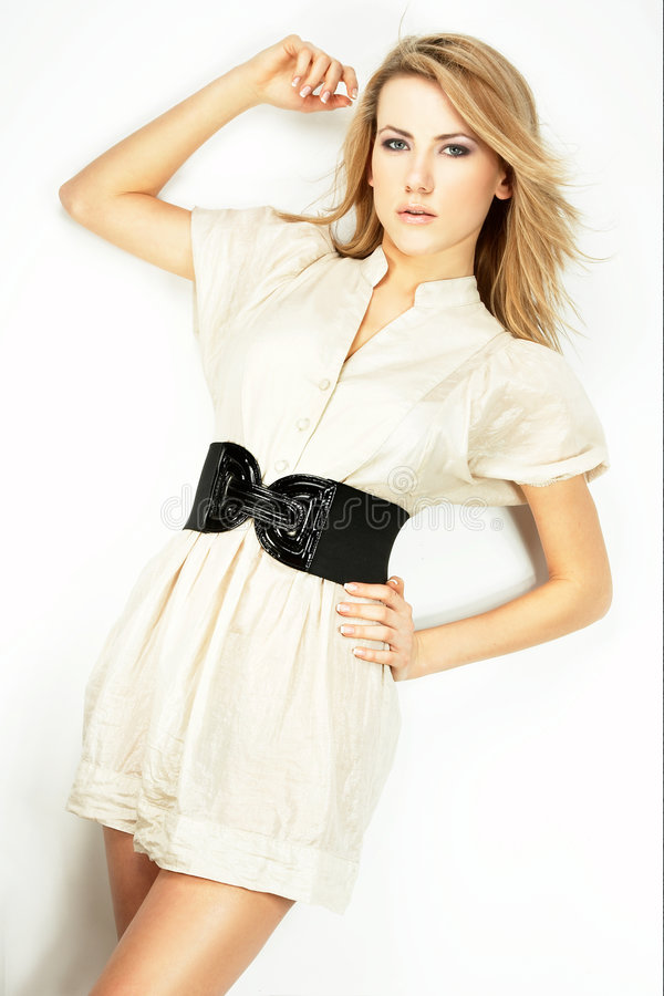 Fashion model Posed on light background. In white dress stock image