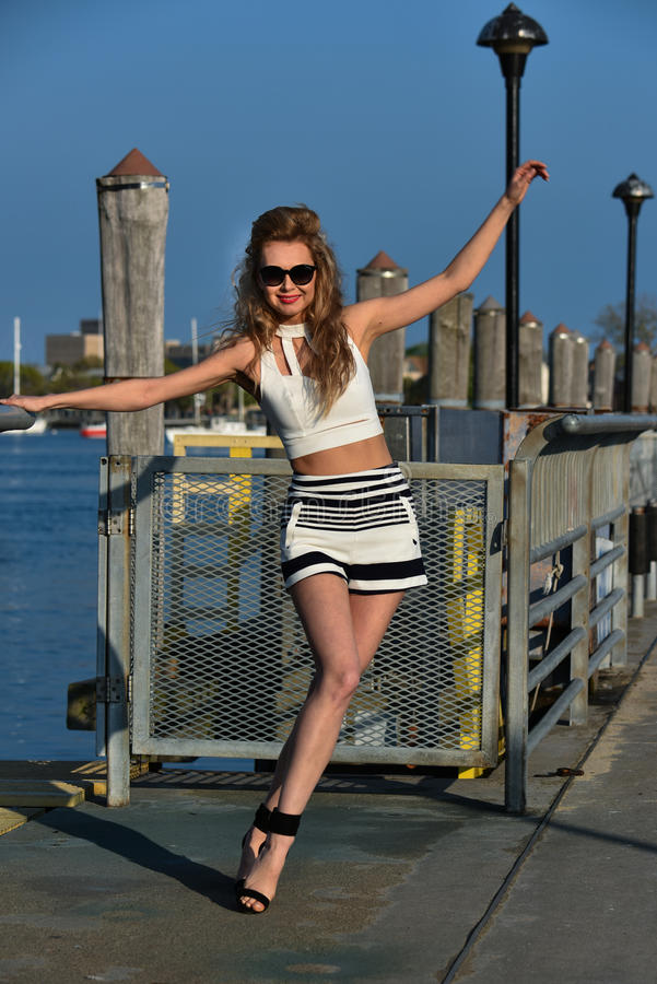 Download Fashion Model Posing Pretty On The Pier In Sunny Weather Wearing White Top, Sailor Shorts And Sunglasses. Stock Image - Image of blond, leisure: 71429937