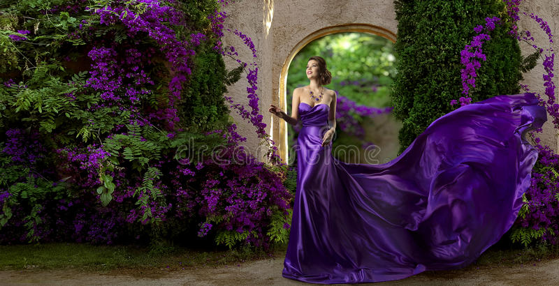 Fashion Model Purple Dress, Woman Long Silk Gown, Violet Garden. Flowers, Flying Fabric stock photography