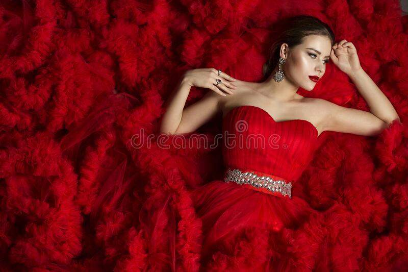 Fashion Model on Red Background, Beautiful Woman Posing on Wavy Fabric Background. Fashion Model on Red Background, Beautiful Woman Posing on Waving Fabric stock photography