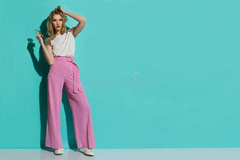 Fashion Model In Red Striped Wide Leg Trousers Standing Aginst Turquoise Wall royalty free stock photos
