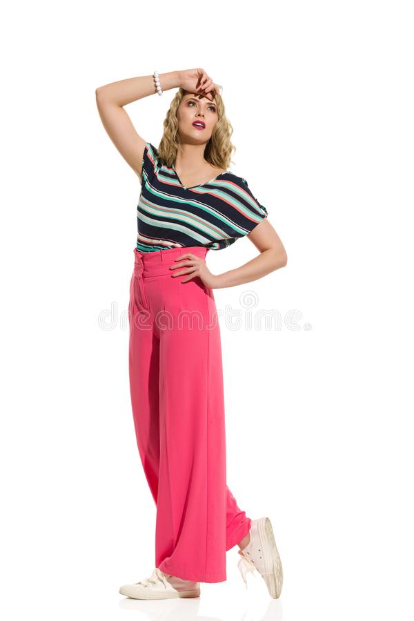 Stylish Young Woman In Red Wide Leg Trousers Is Posing In The Sunlight royalty free stock image