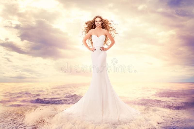 Fashion Model in Sea Waves, Beautiful Woman in Elegant White Dress Hairstyle Waving on Wind, Art Portrait. Over ocean landscape background royalty free stock photo