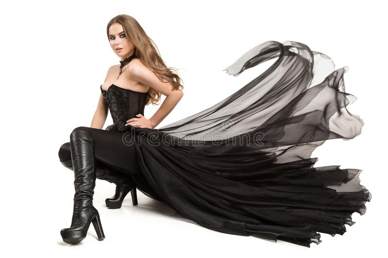 Fashion Model sitting in Black Dress, Fashion Model Corset Dress Leather Boots High Heels on White. Fashion Model sitting in Black Dress, Fashion Model Corset stock photos