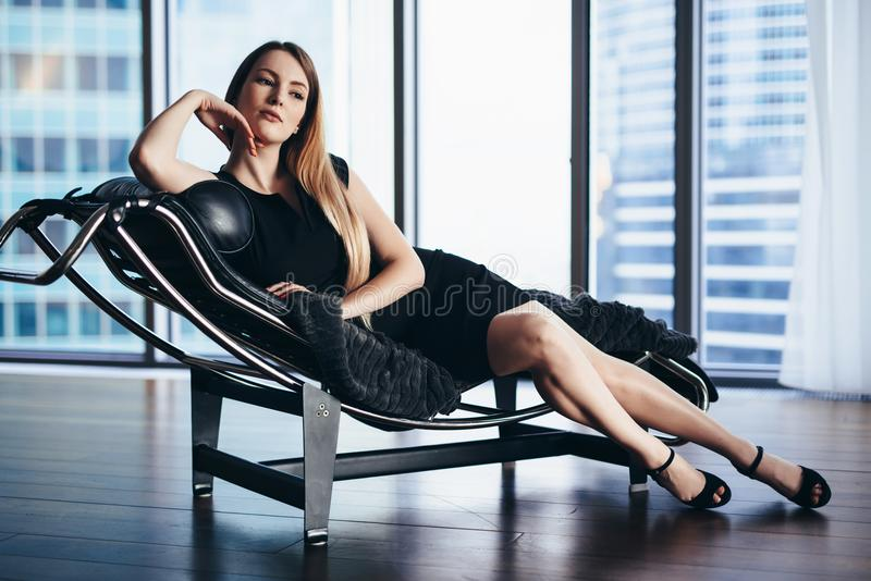 Fashion model with slim long legs wearing black cocktail dress lying on lounge chair in penthouse apartment stock photo