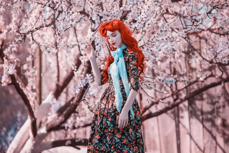Fashion model in spring flower garden. Valentine day background. Retro dress. Fabulous redhead lady in dress. Woman in blue ribbon royalty free stock photos