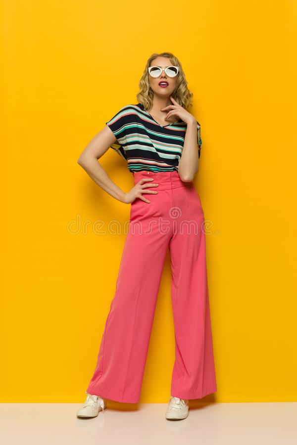 Fashion Model Standing Against Yellow Wall In Pink Wide Legs Trousers And Sunglasses. Young woman in sunglasses and striped blouse and pink wide legs trousers is royalty free stock photography