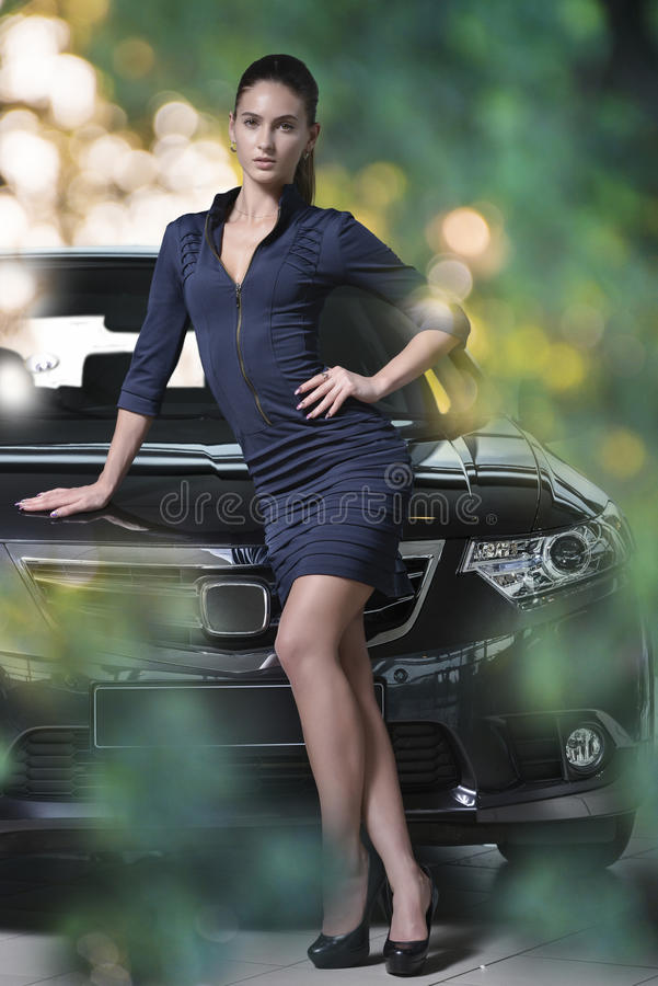 Fashion model standing next to fancy car, blurred green color bubbles background royalty free stock photos