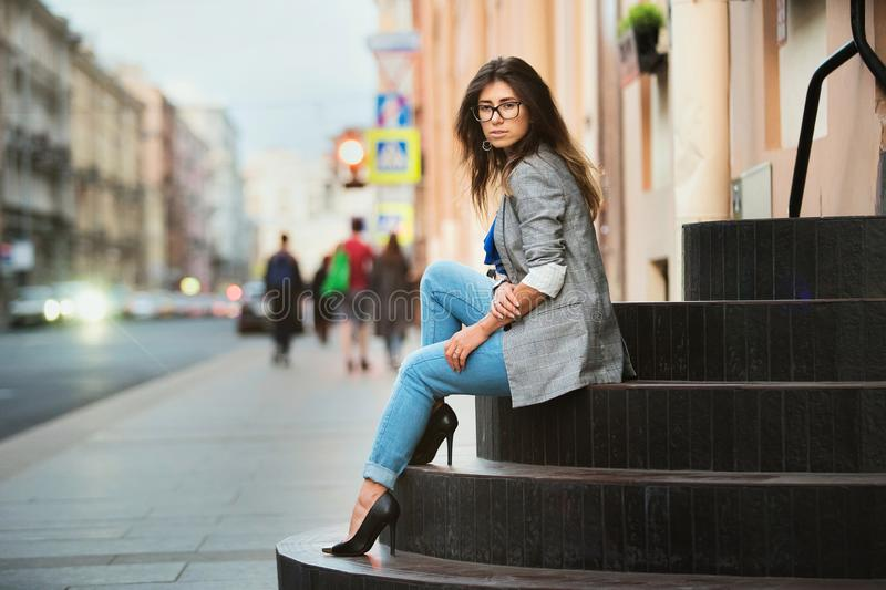 Fashion Model In Street. Beautiful Sexy Woman In Stylish Fashionable Fall Clothes sitting on stairs. In summer. Girl In High Fashion Autumn Clothing Posing royalty free stock photography