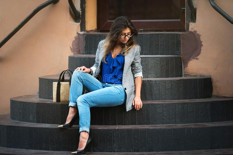 Fashion Model In Street. Beautiful Sexy Woman In Stylish Fashionable Fall Clothes sitting on stairs. In summer. Girl In High Fashion Autumn Clothing Posing stock images