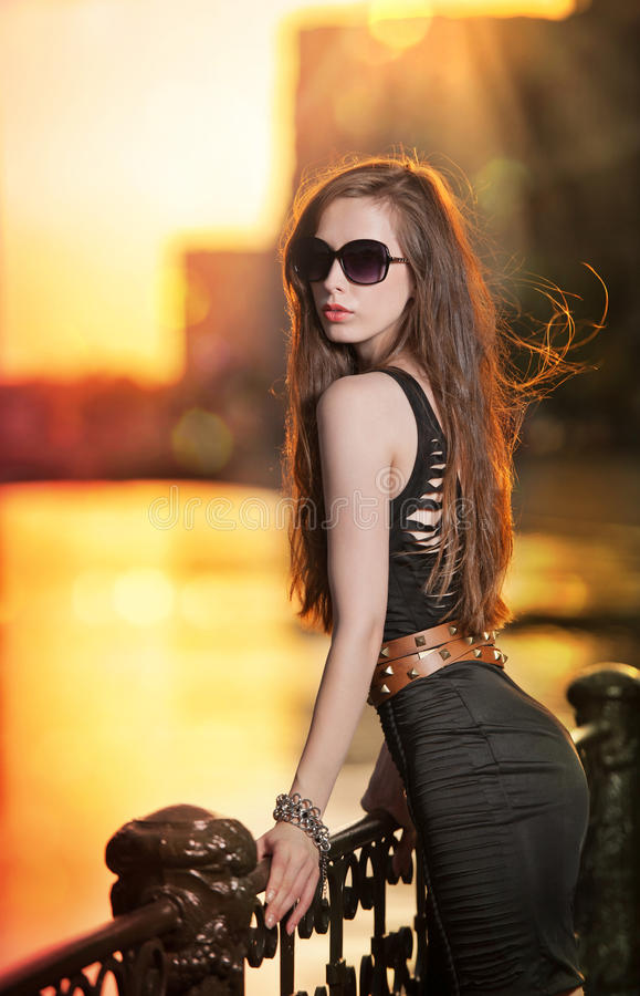 Fashion model on the street with sunglasses and short black dress. Fashionable girl with long legs posing on street.High fashion urban portrait of young, slim stock photography