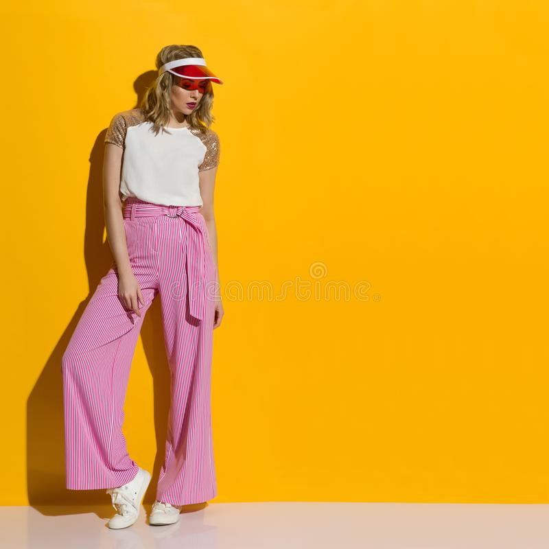 Fashion Model In Striped Wide Legs Trousers And Transparent Sun Visor Is Standing In The Sunlight. Fashion model in striped wide legs trousers and transparent royalty free stock images