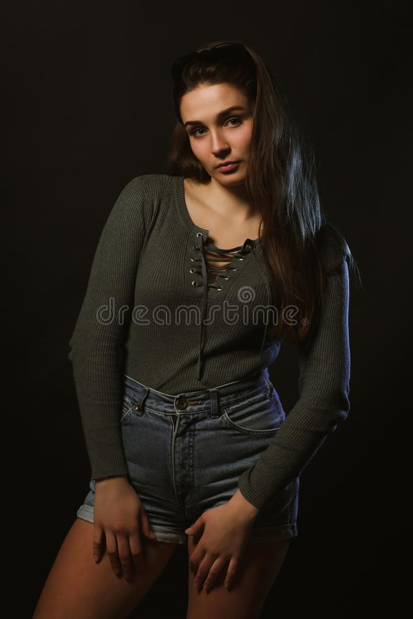 Fashion model test shoot of attractive girl posing in dark studio dressed in grey underwear and jeans shorts royalty free stock photography