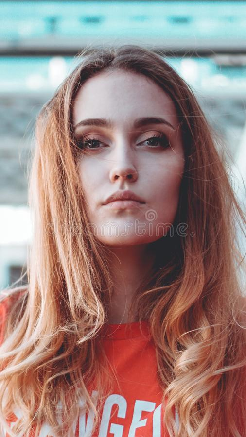 Fashion model wearing red hoodie with inscription los angeles posing at parking stock images